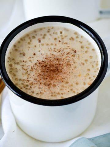 This is a white mug with sago porridge inside.