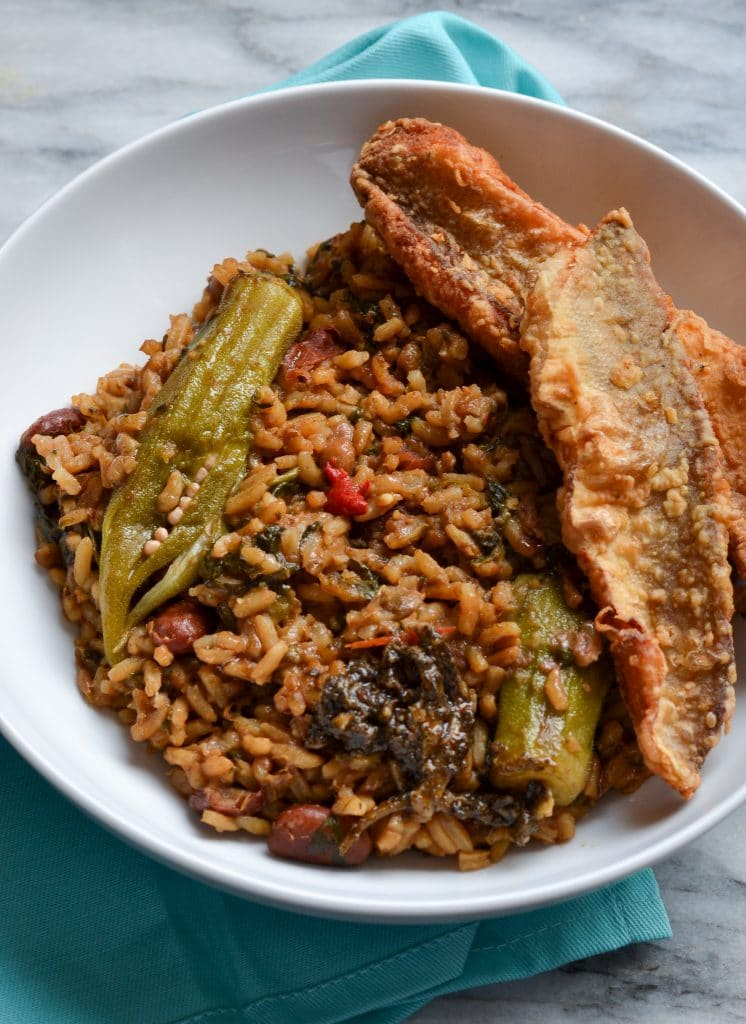 This is an image of guyanese cookup rice with okra and fried fish on the side in a white bowl